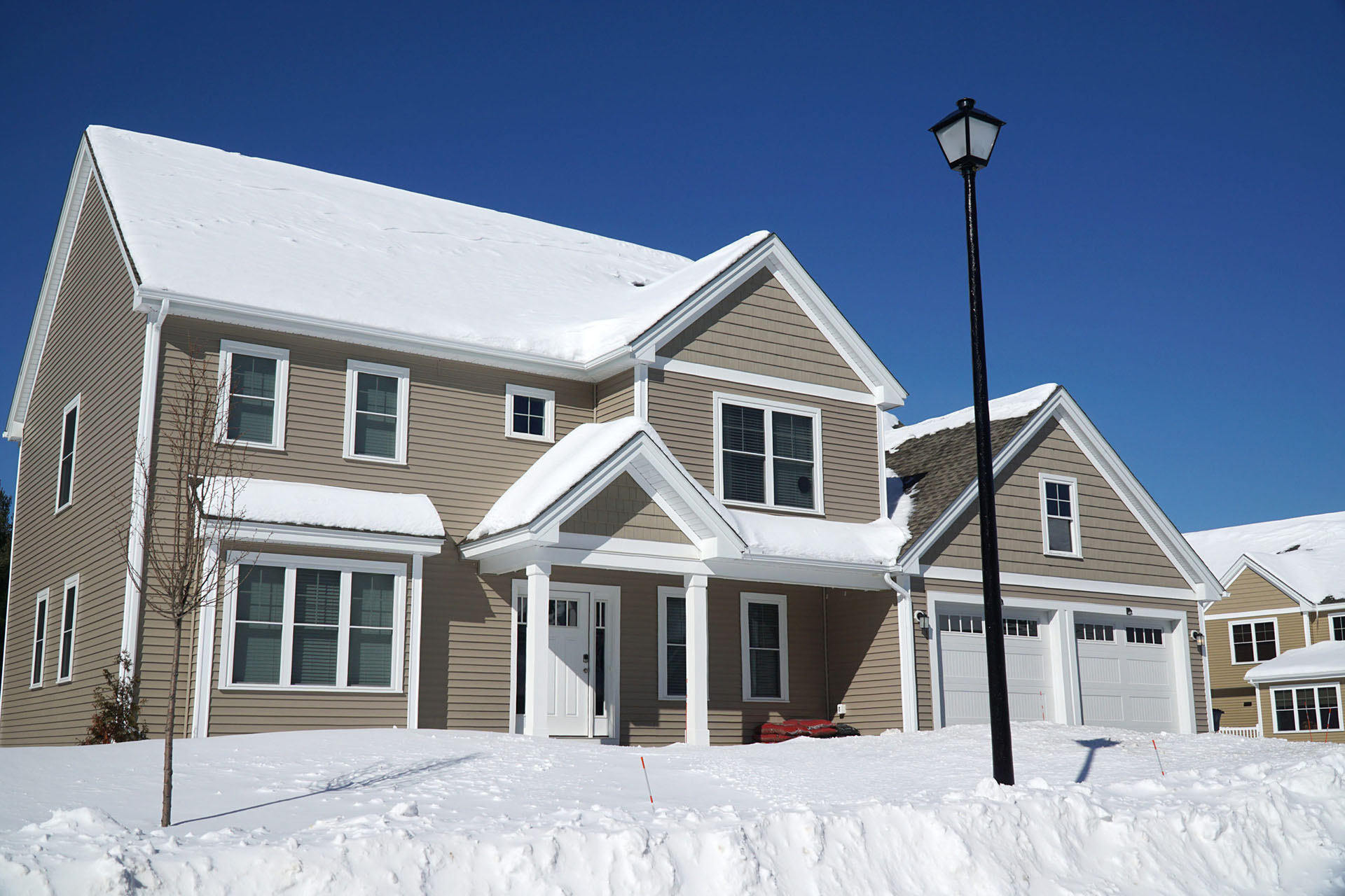 Snow-covered home with tan siding
