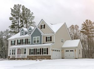 Large home with off-white siding covered with snow