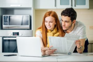Couple holding papers and looking at laptop screen