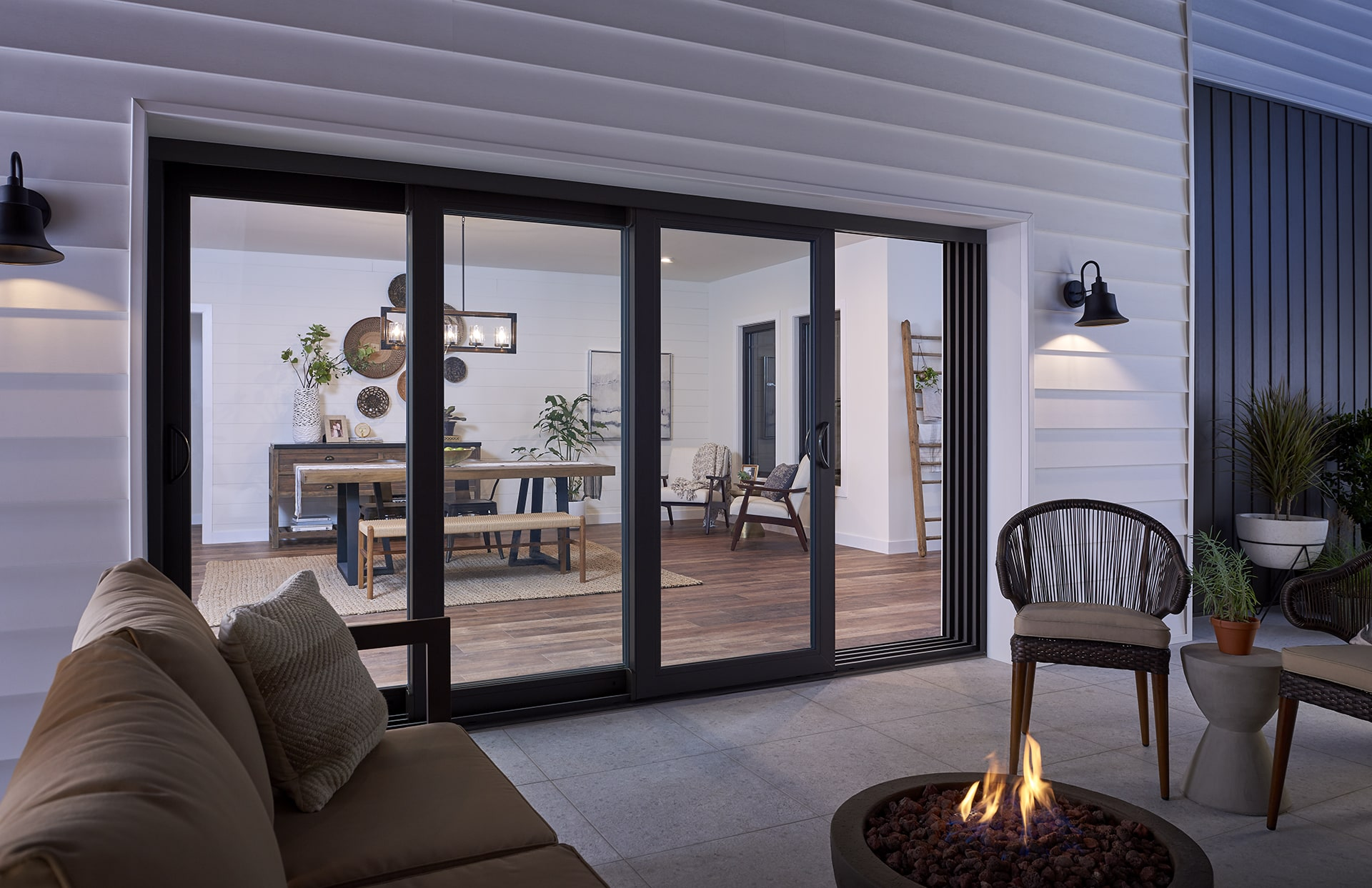 Black French rail door opens to modern patio with fire pit