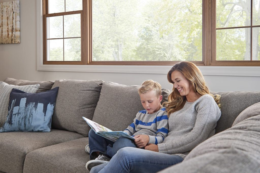 Mother and son reading book in front of bay window