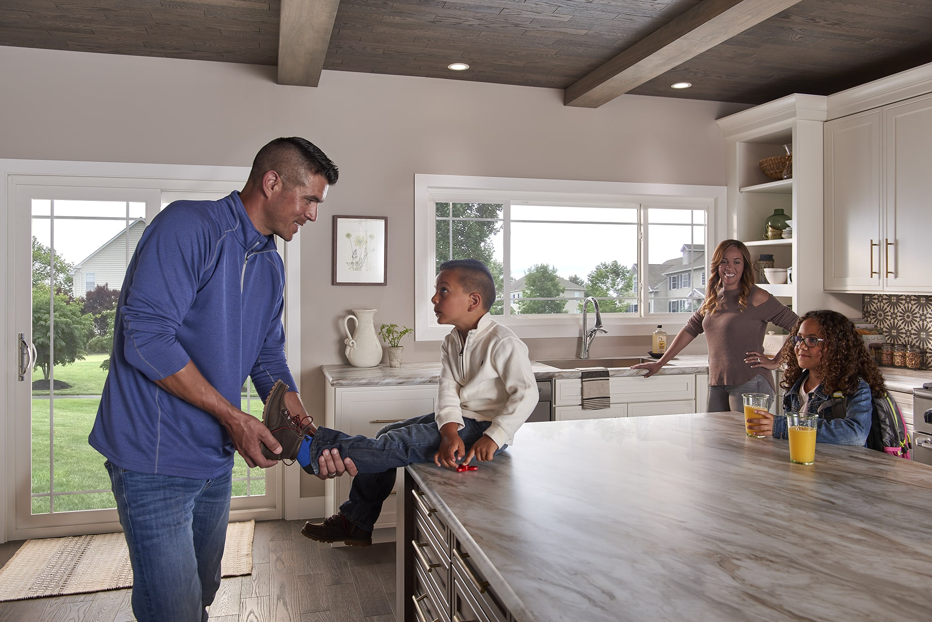 Family congregating in luxurious kitchen