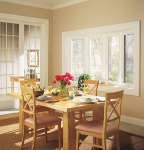 Light streams into dining room from bay and bow window.