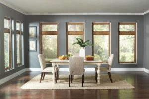 Dining room brightened by natural light from casement windows.