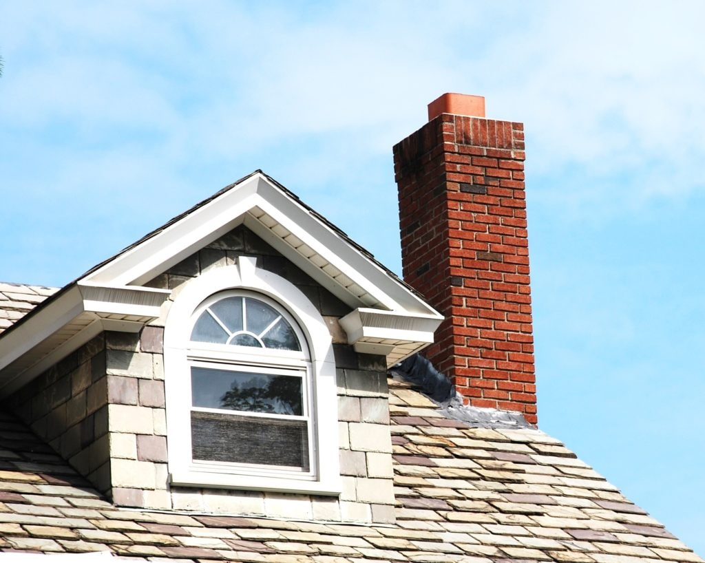 Close up chimney on the roof featuring geometric shaped window.