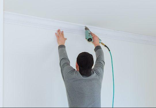 man installing crown molding