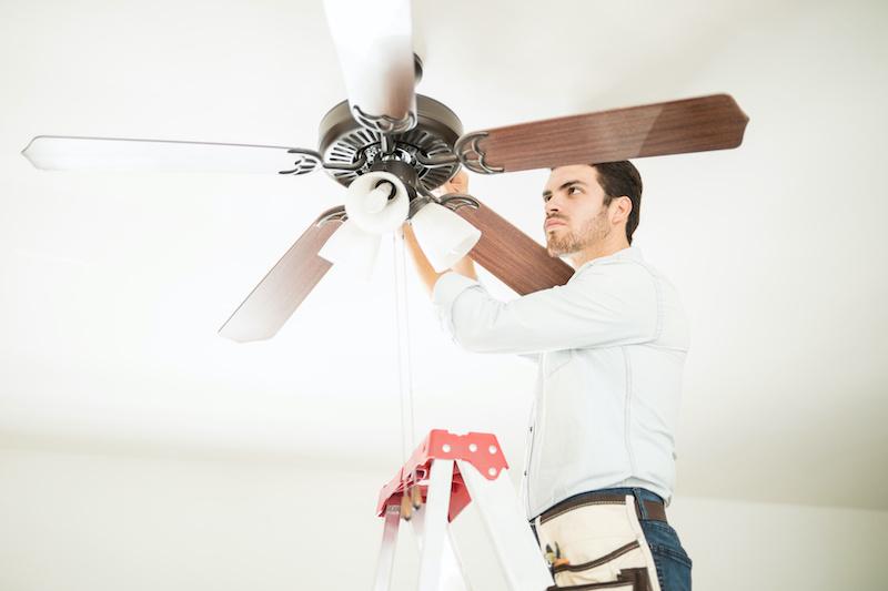 man installing ceiling fan