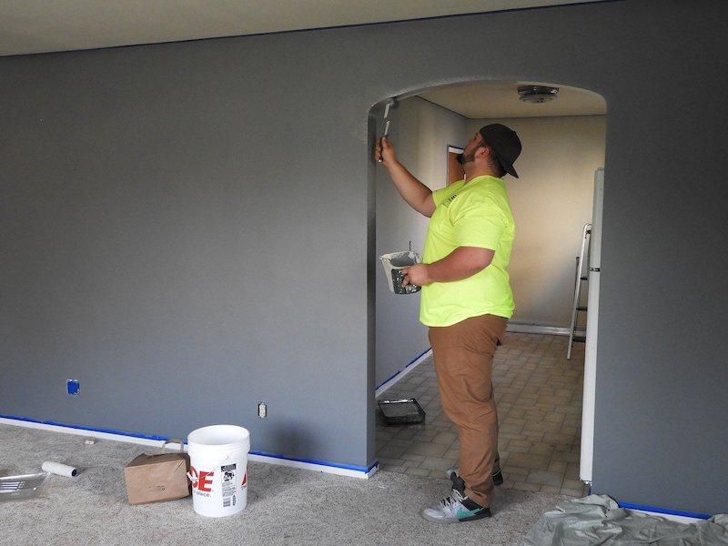 man painting inside of door frame