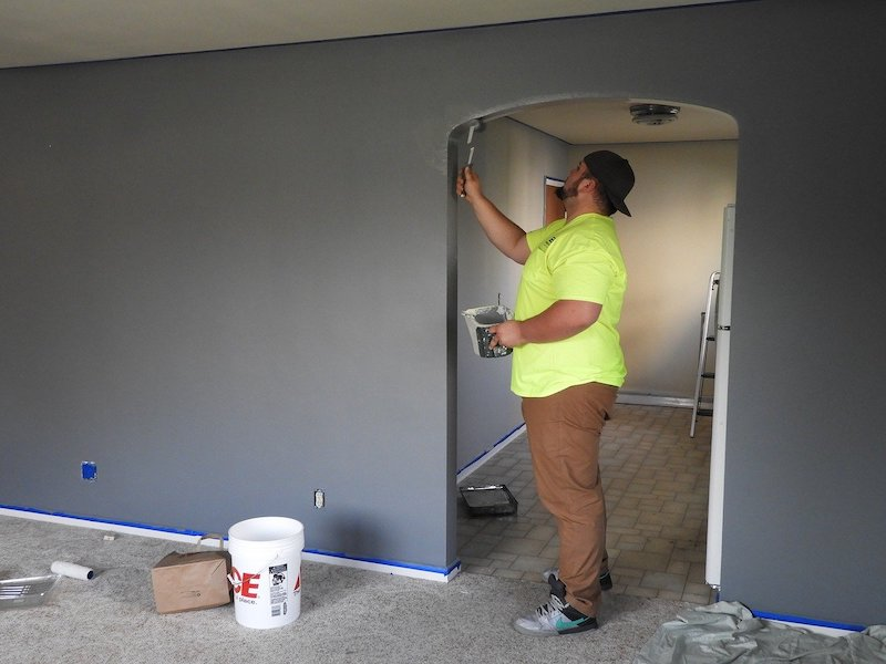 man painting inside of doorway