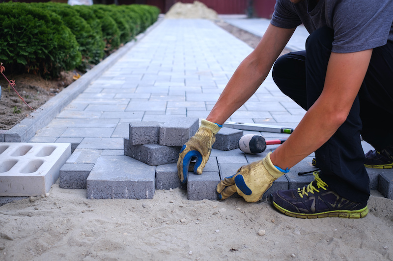 person laying pavers