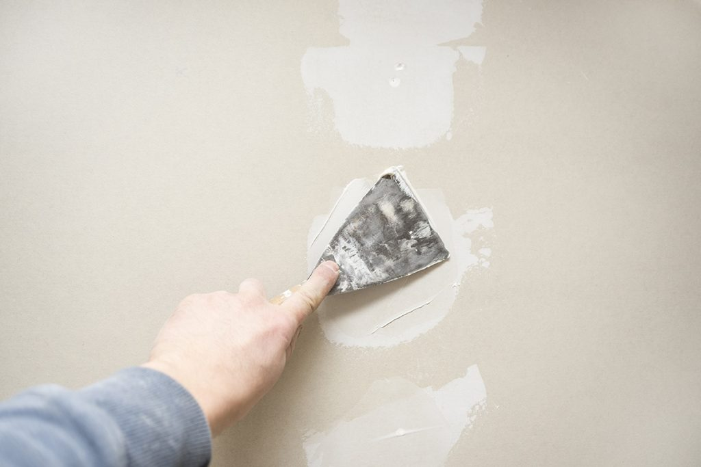 person fixing drywall