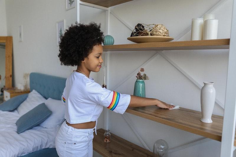 child dusting shelves