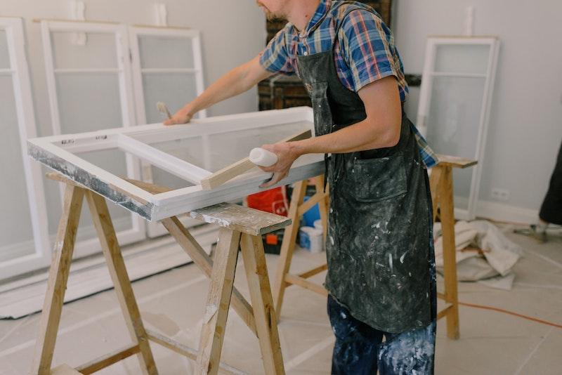 man painting window