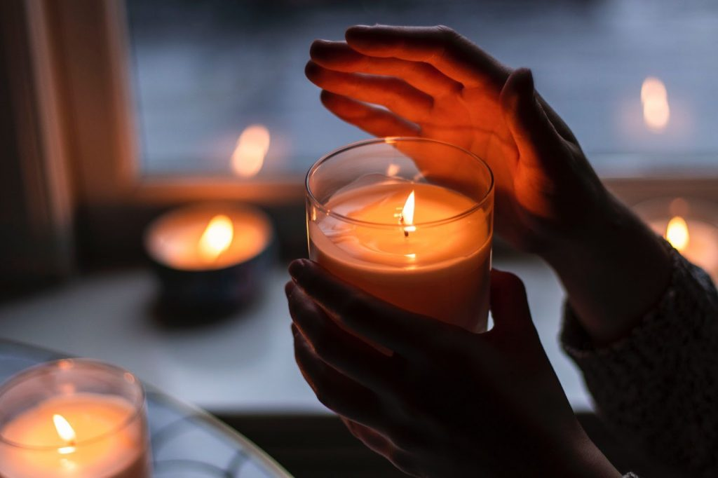person holding small candle during power outage